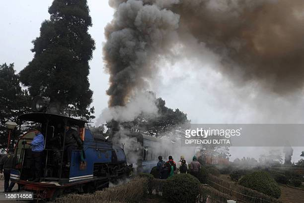 Indian railway workers drive a 'toytrain' past spectators as a part of promotional event of The Darjeeling Tea and Tourism Festival in Darjeeling on...