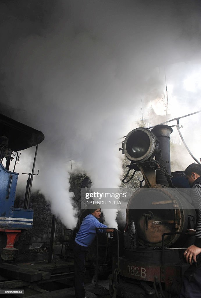 Indian railway workers maintain a steam engine of the Darjeeling Himalayan Railway train, locally known as toy train, in Darjeeling on December 22, 2012. The economy of the eastern Indian state of Sikkim is being buoyed by the ever increasing numbers of foreign and domestic tourists keen to view the mountains of the Himalayan mountain range. AFP PHOTO/ Diptendu DUTTA