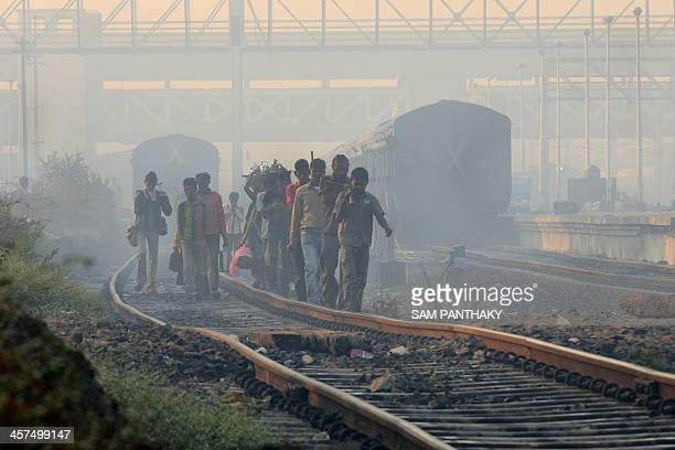 Indian railway workers walk along the tracks at the railway station on a foggy morning in Ahmedabad on December 18 2013 Fog has caused disruption to...