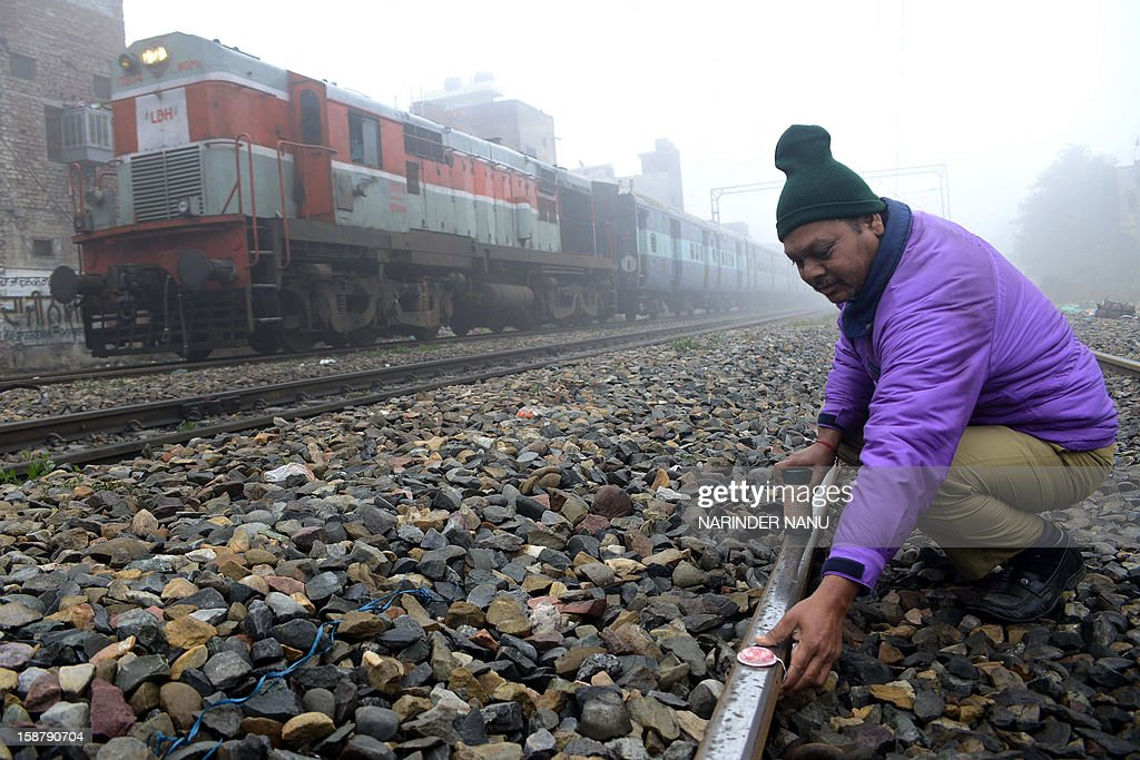 Indian Railways employees Laveinder places 'fog signals' on a railway track as a train passes by in dense fog near a railway station in Amritsar on December 29, 2012. The signals are designed to alert the train drivers in times of dense fog. Heavy fog has distrupted road, rail and air traffic across northern India.