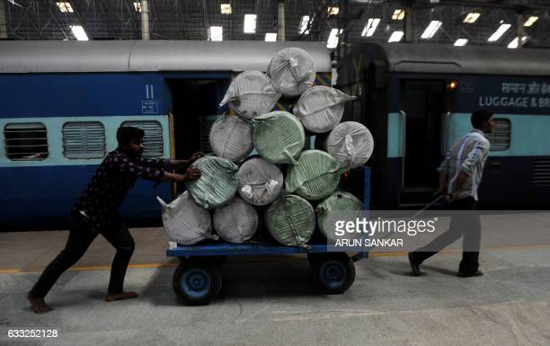 Indian railways workers use a cart to transport goods through a train station in Chennai on Febuary 1 2017 India is to halve the basic rate of income...