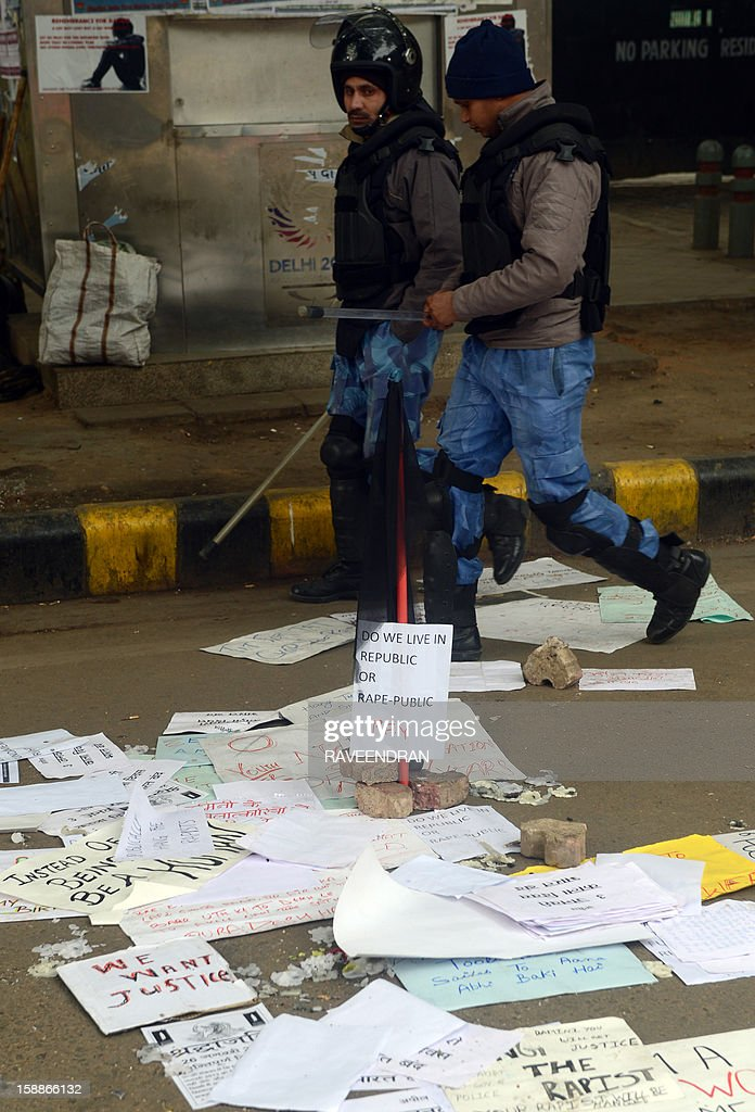 Indian Rapid Action Force (RAF) police officials walk in front of a black flag and poster left by protestors in New Delhi on January 2, 2013. The family of an Indian gang-rape victim said that they would not rest until her killers are hanged as police finalised their investigation before charges are laid against suspects this week. As the ruling Congress party reportedly pushed for tougher punishments for sex crimes, including chemical castration, authorities in New Delhi launched a hotline to improve safety for women in a city dubbed 'India's rape capital'.