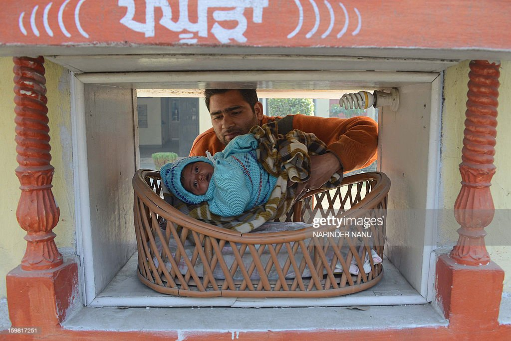 Indian Red Cross Society employee Ashwani Kumar poses with an abandoned baby girl, found at the pictured 'pangpura' (cradle) drop off box at the entrance of the Red Cross House in Amritsar on January 21, 2013. The premises contains a drop off location for unwanted babies, built in 2008, in an attempt to curb female infanticide. An average of 15 babies a year have been saved, according to the society.