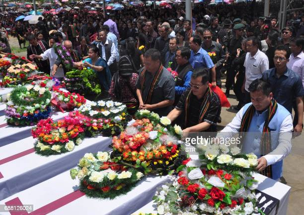 Indian relatives and villagers attend the funerals of eight people killed during protests against the former Congress state government in Manipur on...