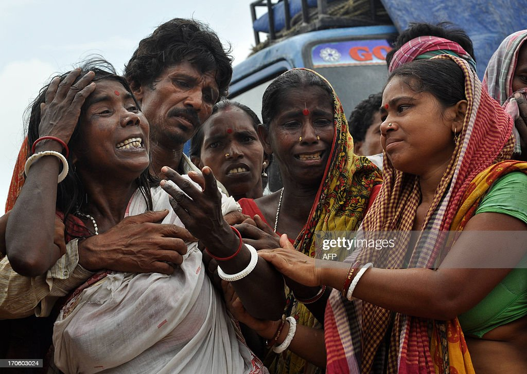Indian relatives mourn as rescue workers carry dead bodies from the Ganges river following a ferry capsizing, carrying passengers and livestock, in Malda district, located 270 kilometres (170 miles) north of Kolkata, on June 15, 2013. The overcrowded ferry capsized on June 14, killing at least ten and leaving 20 others missing, officials said. AFP PHOTO/ Surajit ROY