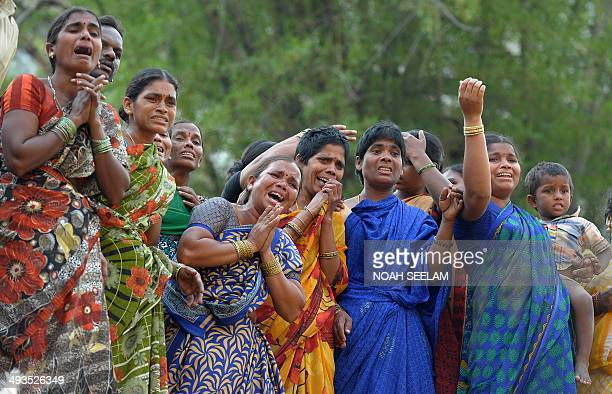 Indian relatives react as they stand near to the bodies of labourers recovered from the rubble of a construction site in Secunderabad on May 24 2014...