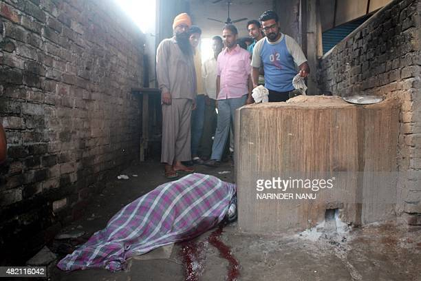 Indian relatives stand near the body of a man identified as Dharshan Lal who was killed during an attack by militants on a police station in...