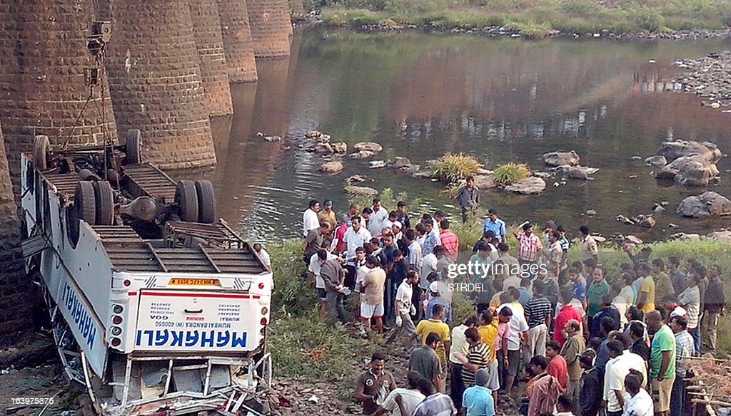 Indian rescue officials and bystanders gather around the wreckage of a bus after it fell from a bridge at Khed, some 350 kilometers (220 miles) south of Mumbai on March 19, 2013. A bus crash left 32 people dead and another 13 injured after the vehicle careered off a bridge into a dry river-bed in India's western state of Maharashtra, police said.