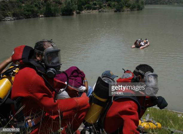 Indian rescue personnel gather on the banks of the Beas River during a search operation in Kullu on June 9 2014 Rescuers discovered five bodies in a...