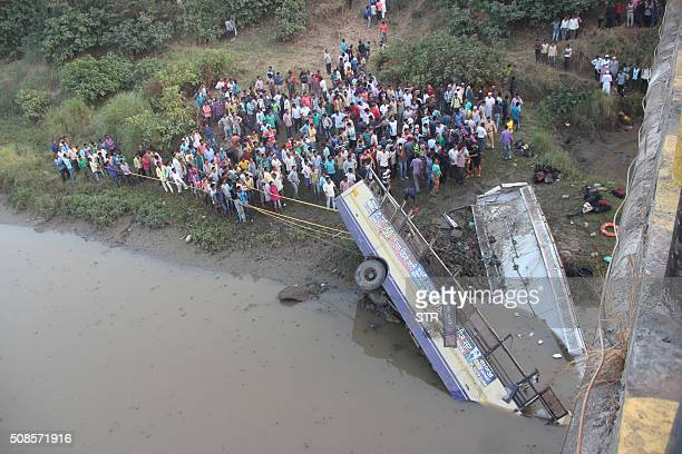 Indian rescue workers and villagers try to extract the injured and dead passengers from a Gujarat State Road Transport Corporation's passenger bus...