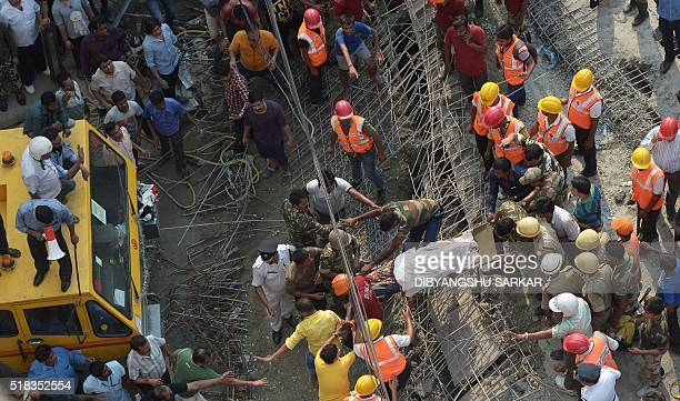 Indian rescue workers and volunteers carry away a body next to the wreckage of a collapsed flyover bridge in Kolkata on March 31 2016 At least 14...