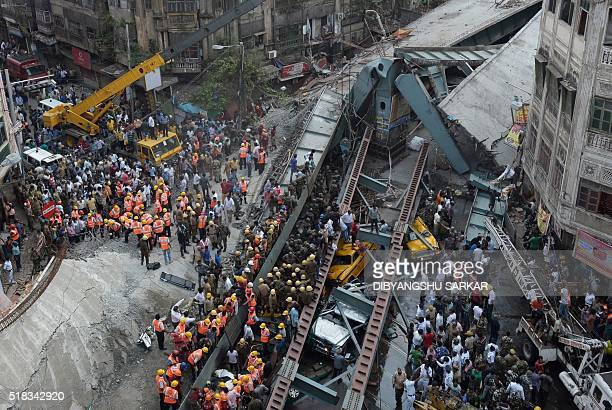 TOPSHOT Indian rescue workers and volunteers try to free people trapped under the wreckage of a collapsed flyover bridge in Kolkata on March 31 2016...