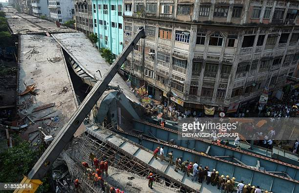 Indian rescue workers and volunteers try to free people trapped under the wreckage of a collapsed flyover bridge in Kolkata on March 31 2016...