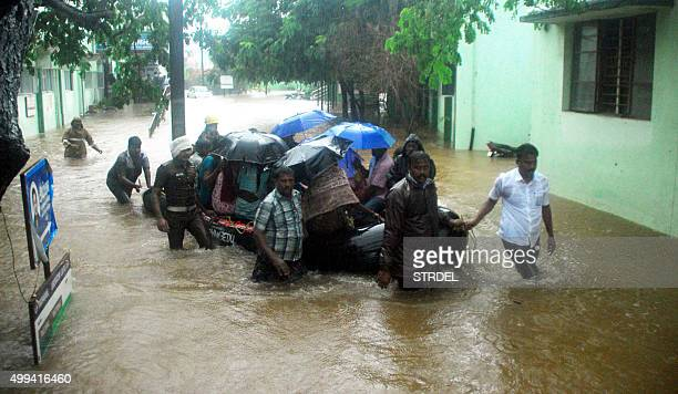 Indian rescue workers and volunteers use an inflatable boat to take residents through floodwaters in Chennai on December 1 during a downpour of heavy...