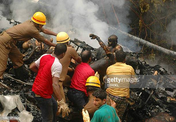 CONTENT Indian rescue workers and volunteers work in the wreckage of an Air India Boeing 737800 aircraft which crashed upon landing in Mangalore on...