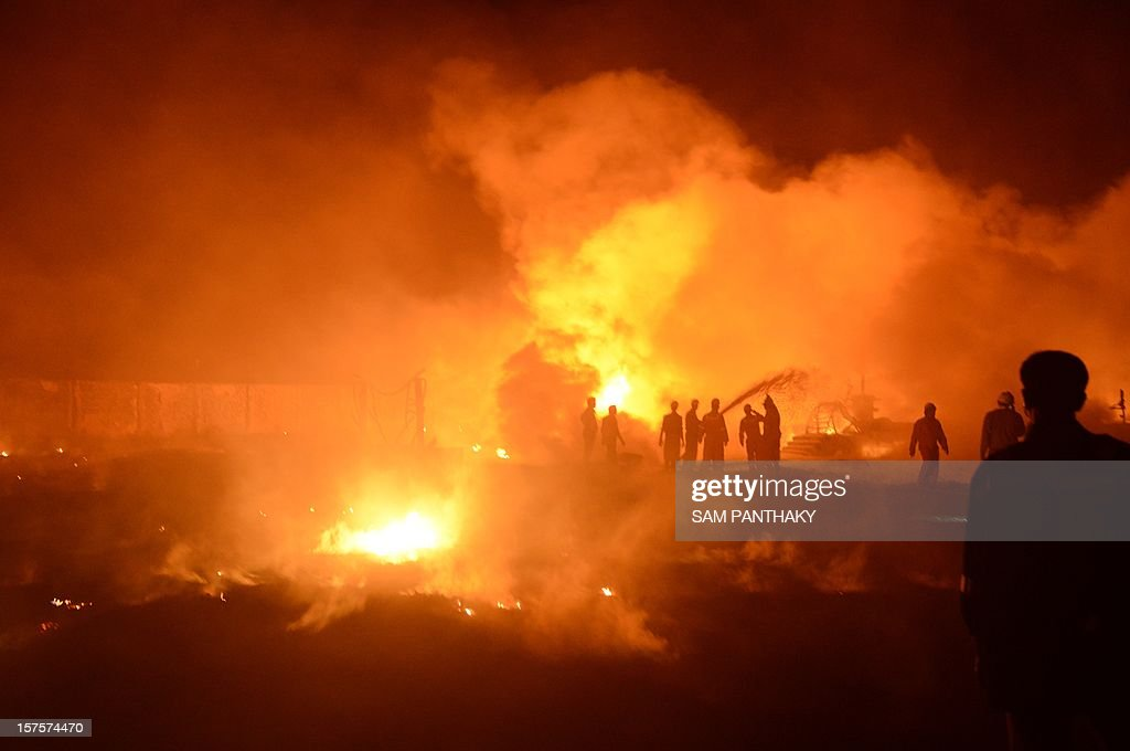 Indian rescue workers attempt to control a major fire that erupted along the Indian Oil Corporation's Crude Oil Pipeline from Salaya to Mathura, at the level of the Rutadal village, some 90 kms from Ahmedabad, late on December 4, 2012. Three persons were injured due to the fire and were later shifted to a hospital in Ahmedabad. Investigations are under way to determine the exact cause of the fire. AFP PHOTO / Sam PANTHAKY