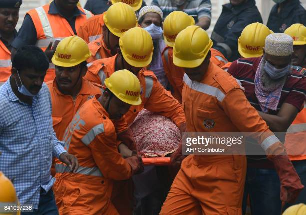 Indian rescue workers carry a victim's body from the building collapse site in Mumbai on August 31 2017 At least three people died and dozens were...