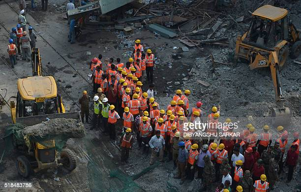 Indian rescue workers clear away debris amid efforts to free people trapped under the wreckage of a collapsed flyover bridge in Kolkata on April 1...