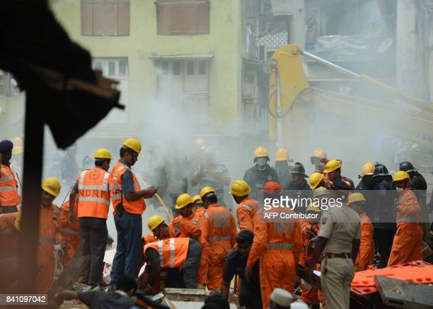 Indian rescue workers look for survivors at the building collapse site in Mumbai on August 31 2017 At least three people died and dozens were feared...