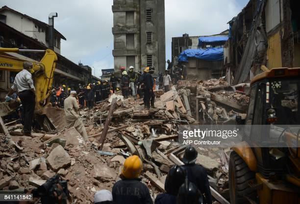 Indian rescue workers look for survivors in the debris of a collapsed building in Mumbai on August 31 2017 At least 12 people died August 31 when a...
