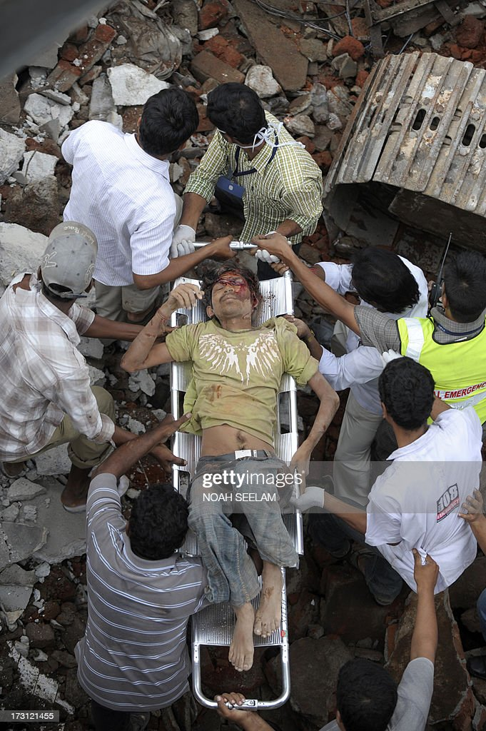 Indian rescue workers move a victim from the rubble at the site of the City Light Hotel building collapse in Secunderabad, the twin city of Hyderabad on July 8, 2013. A two-storey hotel collapsed in the southern Indian city of Secunderabad on July 8, killing five restaurant workers and injuring 15 others, a local police official told AFP. AFP PHOTO / Noah SEELAM