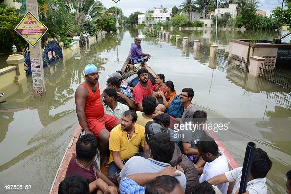 Indian rescue workers on a boat move people to safety amidst waterlogged houses in a flooded suburb of Chennai on November 17 2015 India has deployed...