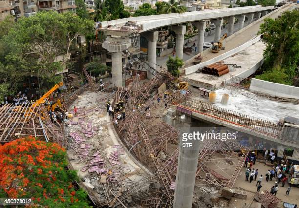 Indian rescue workers search for people under the debris after a huge portion of an underconstruction flyover bridge collapsed in Surat some 260 kms...