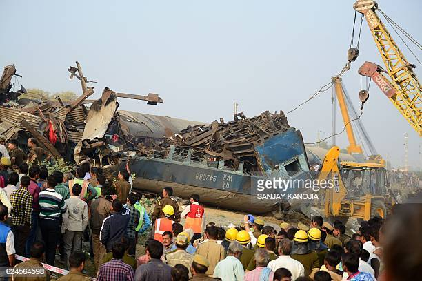 TOPSHOT Indian rescue workers search for survivors in the wreckage of a train that derailed near Pukhrayan in Kanpur district on November 20 2016 A...