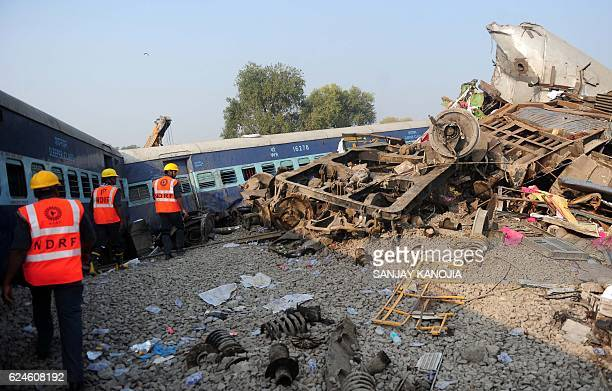 Indian rescue workers search for survivors in the wreckage of a train that derailed near Pukhrayan in Kanpur district on November 20 2016 A passenger...