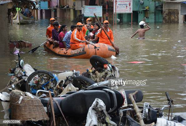 Indian rescue workers transport residents through floodwaters in Chennai on December 4 2015 Thousands of rescuers are racing to evacuate victims of...