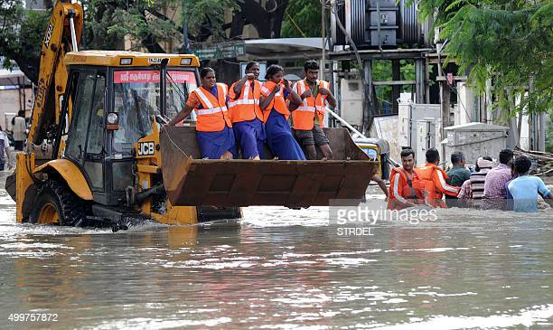 Indian rescue workers travel in the bucket of a bulldozer as they navigate through floodwaters in Chennai on December 3 2015 Thousands of rescuers...