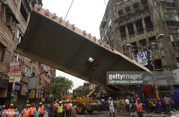 TOPSHOT Indian rescue workers try to free people trapped under the wreckage of a collapsed flyover bridge in Kolkata on April 1 2016 Emergency...