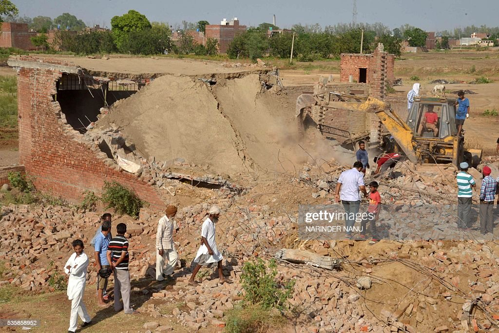 Indian rescue workers use a bulldozer to remove the carcasses of animals from the wreckage of a cattle shed which had collapsed on the outskirts of Amritsar on May 30, 2016, as strong winds and heavy rains lashed the northern Indian city. Some ten animals died and another ten were injured as unseasonal weather systems spread over northern India. / AFP / NARINDER