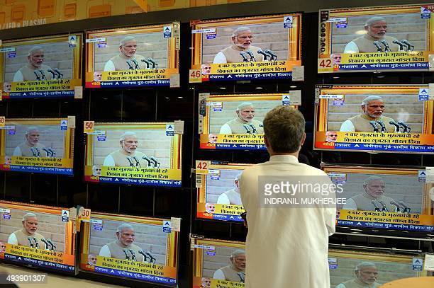 Indian resident Maqbool Alam Siddiqui watches a bank of televisions featuring images of Narendra Modi taking his oath as India's Prime Minister in...