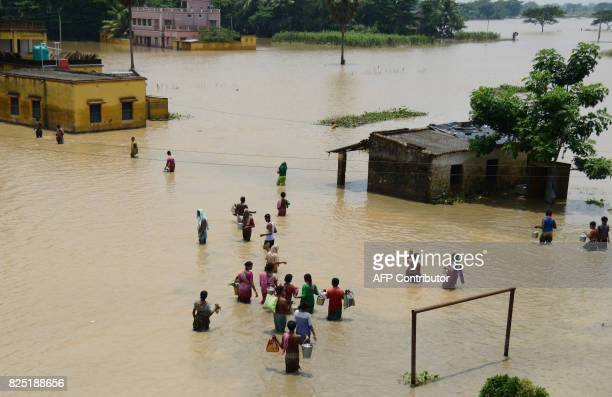 TOPSHOT Indian residents affected by flooding naviagate flodwaters to collect relief materials in Udaynarayanpur some 83kms west of Kolkata on August...