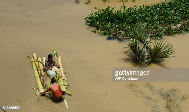 Indian residents affected by flooding use a makeshift boat to naviagate flodwaters to collect relief materials in Udaynarayanpur some 83kms west of...