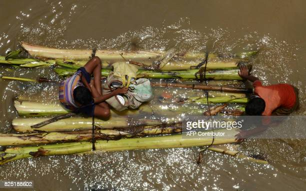Indian residents affected by flooding use a makeshift boat to navigate flodwaters to collect relief materials in Udaynarayanpur some 83kms west of...
