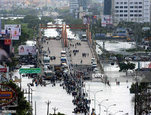 Indian residents and motorists gather on a flyover as others wade through floodwaters in Chennai on December 3 2015 Thousands of rescuers raced to...