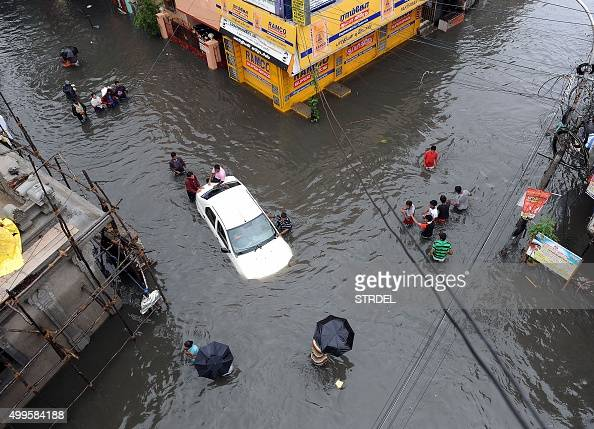 Indian residents attempt to push a vehicle through floodwaters as others wade past in Chennai on December 2 2015 India has deployed troops to Tamil...