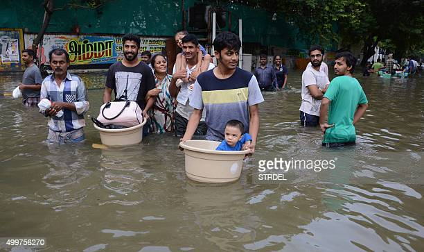 Indian residents carry children and possessions as they walk through floodwaters in Chennai on December 3 2015 Thousands of rescuers raced to...