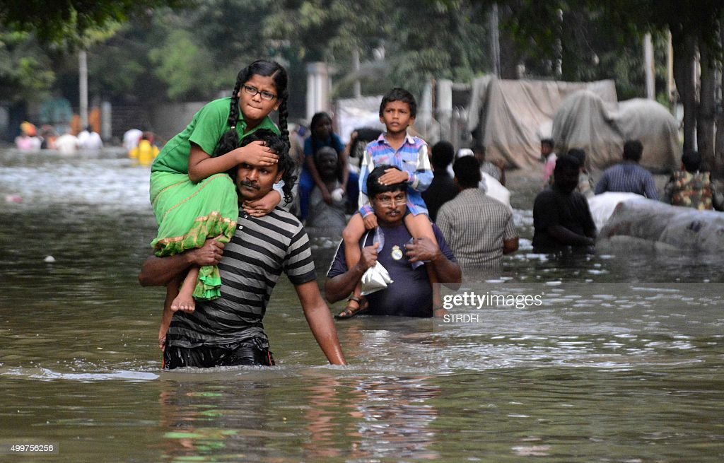 Indian residents carry children as they walk through floodwaters in Chennai on December 3 2015 Thousands of rescuers raced to evacuate residents from...