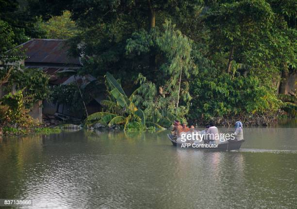 Indian residents carry drinking water for distribution on a boat to flood effected villagers near submerged area in Gazole village at Malda district...