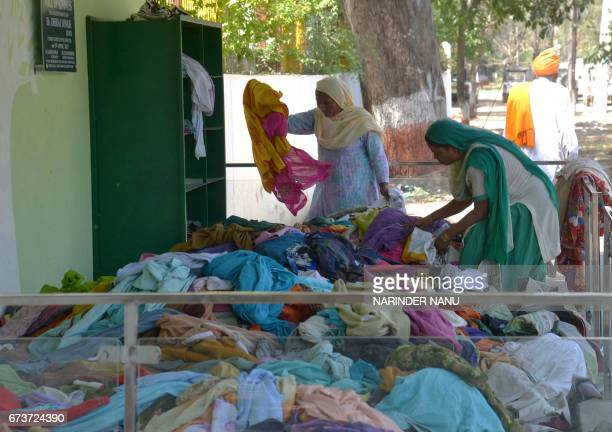 Indian residents collect clothes from a 'Wall of Kindness' in Amritsar on April 27 2017 The 'Wall of Kindness' provides a space where unwanted...