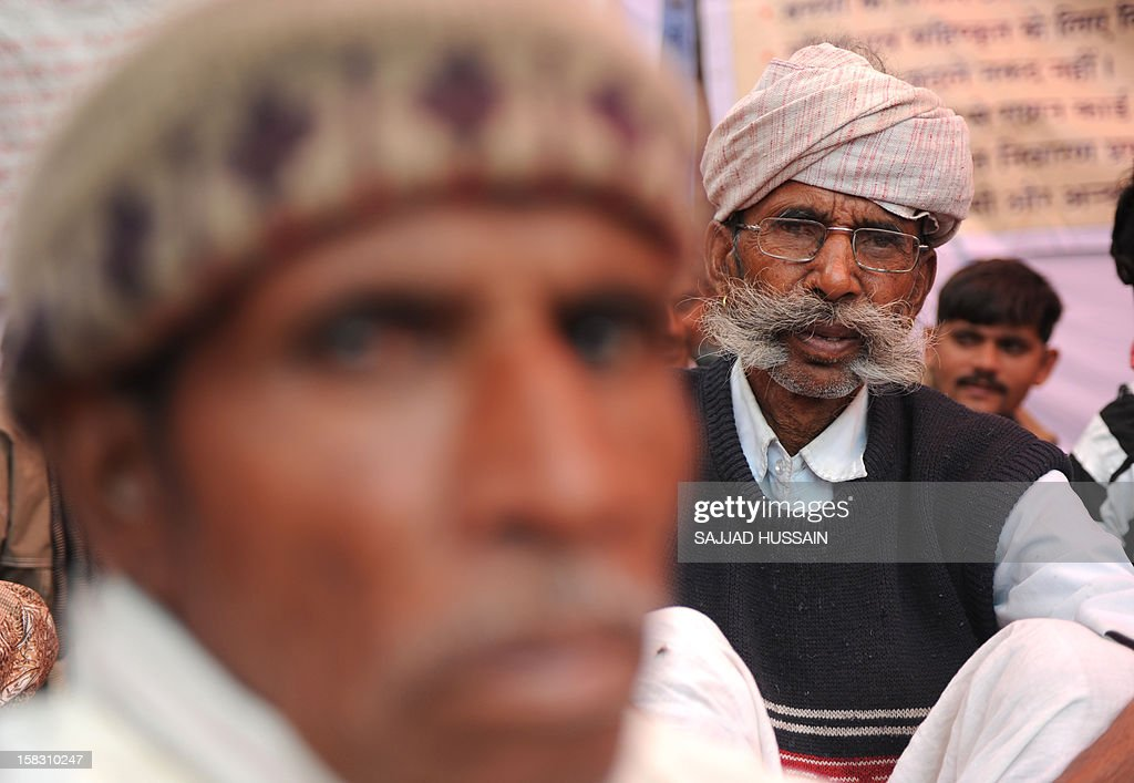 Indian residents from Kotkasim, a block of Alwar district in western Rajasthan state sit during a protest in New Delhi on December 13, 2012. Protesters gathered to oppose a government plan that would transform India's corruption-ridden welfare system by replacing subsidies with direct cash transfers. The ruling Congress party, which is looking to the policy as a vote winner ahead of elections in 2014, has started trials of the scheme and hopes to introduce it nationwide next year. AFP PHOTO/ SAJJAD HUSSAIN