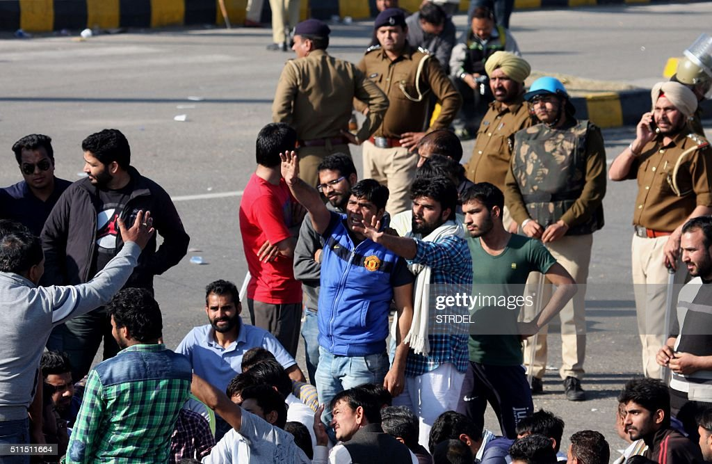 Indian residents from the Jat community block the Chandigarh-Shimla highway as security personnel look on amid violent caste protests in Panchkula on February 21, 2016. Ten people have died in caste protests which triggered widespread arson and looting in a north Indian state, police said February 21, as New Delhi faced a water crisis after mobs shut down a key supply. Thousands of troops with shoot-on-sight orders were deployed on February 20 in Haryana state, a day after week-long protests turned violent with rioters setting fire to homes and railway stations and blocking highways.