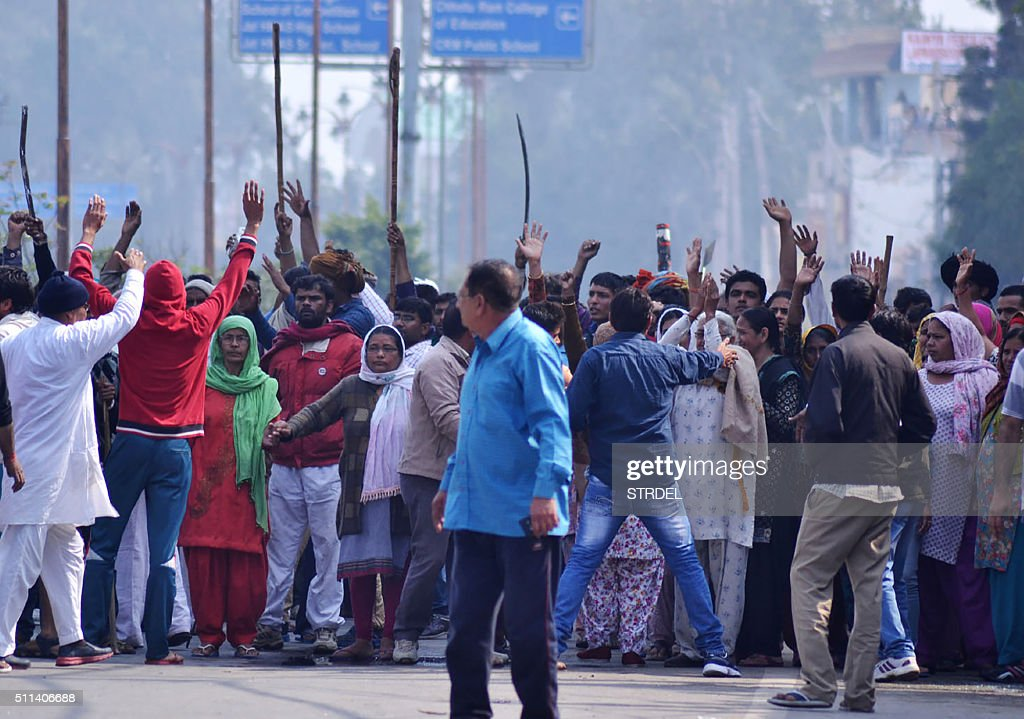 Indian residents gather on a street as others gesture to hold them back amid ongoing caste protests in Rohtak on February 20, 2016. Indian authorities issued shoot-on-sight orders and deployed thousands of troops in a northern state neighbouring New Delhi February 20, after escalating caste protests left at least one dead, officials said. A week-long protest by the state's dominant Jat caste, who are demanding quotas for government jobs and in education, turned violent February 19 as police fired on protesters with local reports saying four had died.