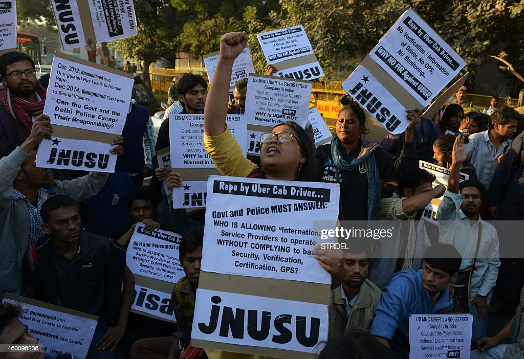 Indian residents hold placards and chant slogans as they take part in a protest against the alleged rape of a passenger by a driver working for the...