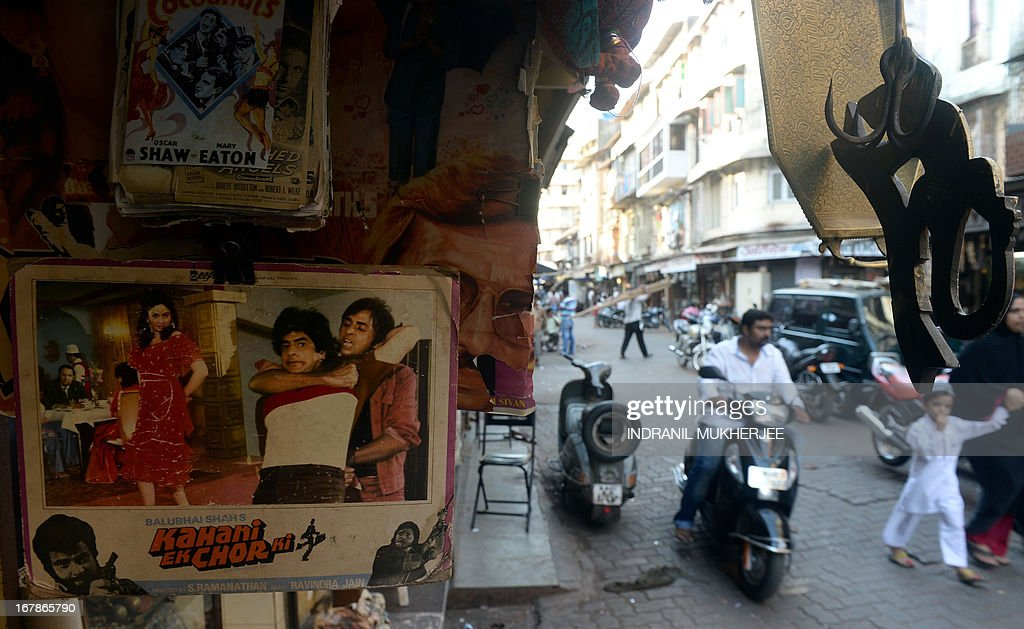 Indian residents journey past a shop selling Bollywood memorabilia in Mumbai on April 30, 2013. One hundred years after the screening of a black-and-white silent film, India's brash, song-and-dance-laden Bollywood film industry celebrates its centenary later this week. The milestone will be marked with little fanfare, while India will be honoured as 'guest country' at next month's Cannes festival.