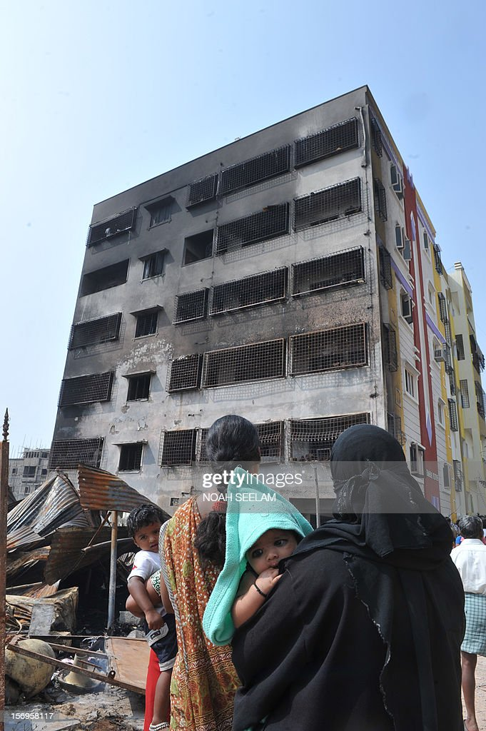 Indian residents look at an apartment that caught fire on the outskirts of Hyderabad on November 26, 2012. Five people including a child died in the blaze, which allegedly started when a makeshift shed nearby burned. AFP PHOTO / Noah SEELAM