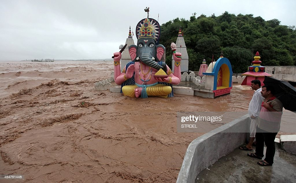 Indian residents look on from a roof as raging waters from the overflowing Tawi river inundate a Hindu Temple in Jammu on September 6 2014 Incessant...